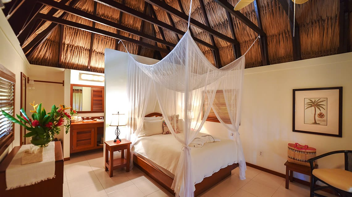 Bedroom in Casita with thatched roof at Victoria House Resort and Spa, Belize