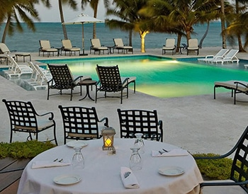 Dining table with white tablecloth overlooking beachfront pool at Victoria House Resort and Spa, Belize