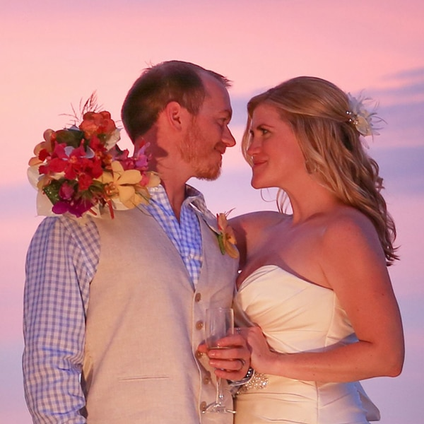 Bride and groom under pink sky in Belize