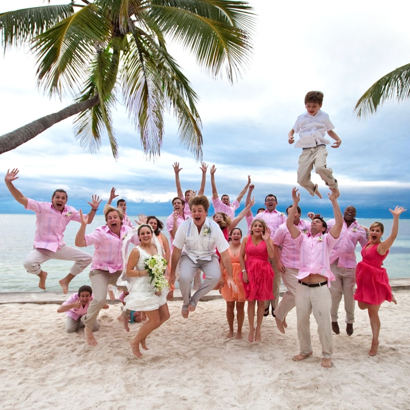 Bridal party celebrating on the beach at Victoria House Resort and Spa
